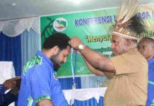 Caption : Asisten I Setda Provinsi Papua, Doren Wakerkwa saat menyematkan tanda peserta sebagai tanda dibukanya Konferensi Luar Biasa di BLKI Papua, Selasa (11/12/2018). Foto : Loy/PapuaSatu.com