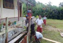 Caption : Terlihat Kanit Binmas Polsek Waris, saat mengajari pelajar SD menanam bunga dan pohon di lingkungan sekolah SD YPPK Epinos