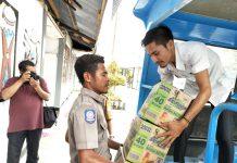 Caption: Staf Pemerintah Kabupaten Keerom saat mengangkut bahan pokok yang akan disumbangkan kepada korban banjir bandang di Sentani Kabupaten Jayapura.