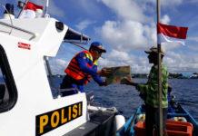 Kasat Pol Air Iptu Nurdin Rahmawati saat membagikan bendera merah putih dan sembako kepada nelayan di perairan Bosnik, BMJ dan perairan pulau Owi
