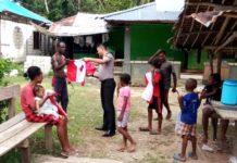 Kapolsek Nimboran Ipda Andi Basuki Rachmat, SH bersama Bhabinkamtibas Kampung Pobaim, Bripka Nataniel Tanan saat membagi bendera Merah Putih kepada warga, Kamis (16/08/18).