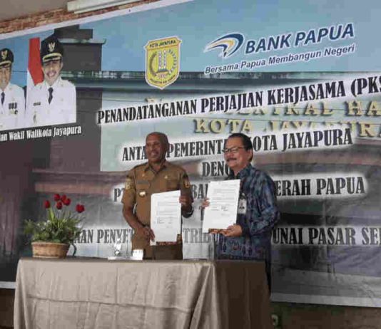 Caption foto : Wali Kota Jayapura Benhur Tomi Mano bersama Direktur utama Bank Papua F Zendrato lakukan MoU dalam pembayaran Non tunai di Pasar Hamadi