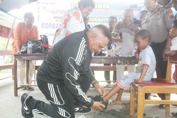 Caption : Penasehat Team Relawan Ikatan Masyarakat Papua Alumni Jawa Timur, Irjen Pol Paulus Waterpauw, saat mengenakan sepatu bagi siwa PAUD di Kampung Puay, distrik Sentani Timur kabupaten Jayapura, Jum'at (17/5/2019).