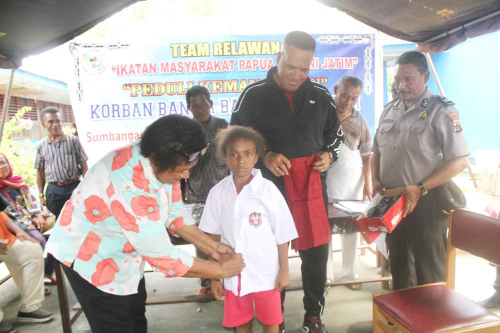 Caption : Dokter Paulina Watopa, salah satu Alumni Jawa Timur saat mengenaikan pakaian seragam kepada siswi SD di Kampung Puay, distrik Sentani Timur Kabupaten Jayapura, Jum'at (17/5/2019).
