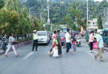 Salah Satu anggota Lantas Polda Papua, saat menyeberangi sejumlah warga di Jalan Protokol depan Polda Papua, pada Kamis (30/05/2019)