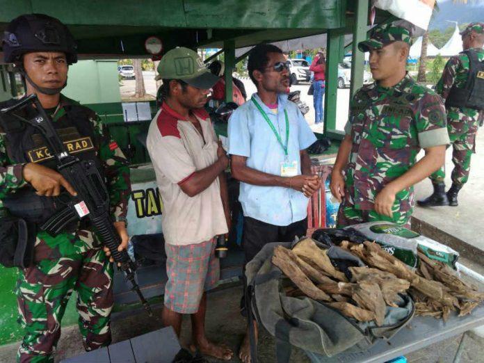 Caption : Satgas Pamtas Yonif Pr 328/Dgh, saat mengamankan salah seorang pria asal PNG karena membawa Kayu Gaharu illegal seberat 19,5 kg.