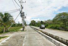 Caption: Tampak tiang listrik milik PLN yang hingga kini belum dipindahkan di jalan Arso Swakarsa.