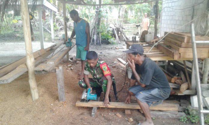 Caption : Babinsa Pos Ramil 1708-02/ Warsa Sertu Firman saat membantu membuat kusen jendela milik warga Kampung Sesur Distrik Yawosi Kabupaten Biak Numfor, Kamis (20/06/2019).