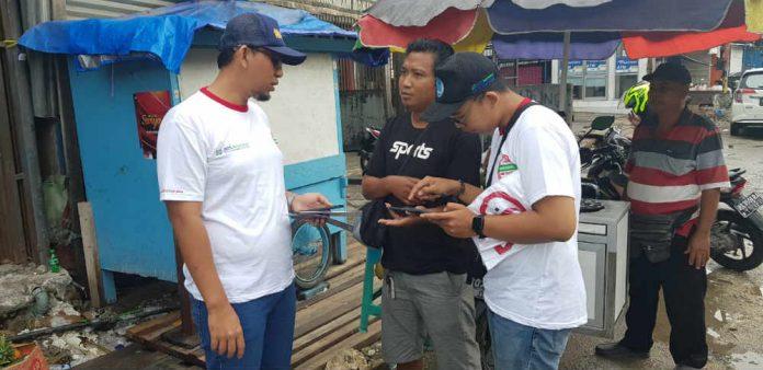 Caption : Kepala Cabang BPJS Kesehatan, Djamal Adriansyah saat mengedukasi tentang program JKN-KIS sambil perkenalkan aplikasi Mobile JKN kepada masyarakat di Pasar Hamadi Jayapura.