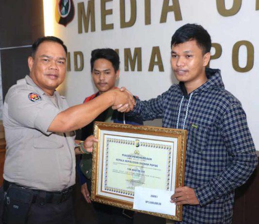 Caption : Kasubbid Penmas Bidhumas Polda Papua Kompol Anton Ampang, saat menyerahkan hadiah pemenang turnamen PUBG MOBILE, Selasa (09/07/2019).