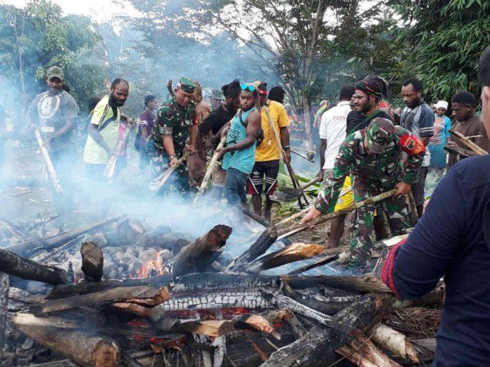 Caption Foto : anggota Kodim 1710/Mimika bersama masyarakat di Kampung Mandiri Jaya Distrik Wania Kabupaten Mimika menggelar acara bakar batu, pada Rabu (10/07/2019).