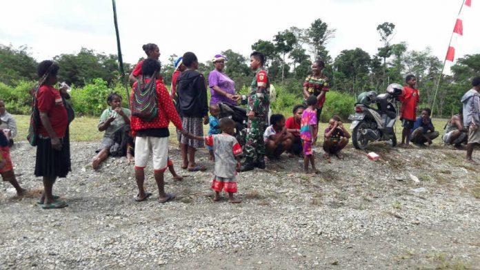 Caption : Babinsa Koramil 1710-02/Timika, saat mengajak warga untuk mensukseskan TMMD ke 1005 di Kampung Mandiri Jaya, Kamis (11/07/2019).