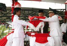 Bupati Keerom Muh. Markum saat menyerahkan bendera Merah Putih kepada petugas pengibar bendera dalam upacara HUT Kemerdekaan Republik Indonesia ke 74 Tahun di Kabupaten Keerom.