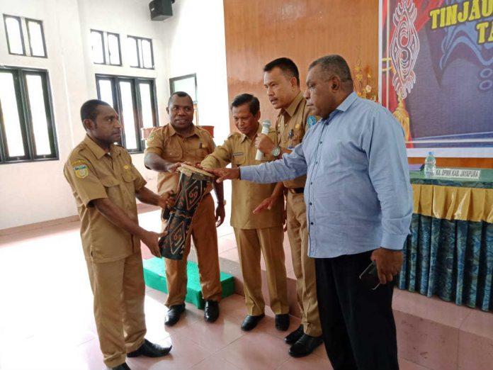 Caption : Wakil Bupati Jayapura, Giri Wijayantoro didampingi Asisten I dan Kepala DPMPK Kabupaten Jayapura, menabuh Tifa sebagai tanda dibukanya Pelatihan Tinjauan APBK dan Penyusunan Draft RKPK Tahun 2020 bagi 14 Kampung Adat, Senin (5/8/2019).