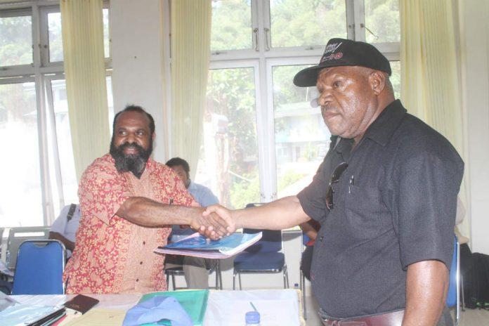 Caption Foto : Koordinator Devisi Logistik KPA Provinsi Papua, saat menyerhakan laporan hasik kerja ke koordinator Devisi SDM Papua, Berni Pagawak