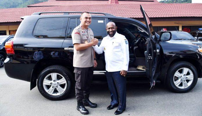 Bupati Mamberamo Tengah, Ricky Ham pagawak,Sh. M.SI. berfoto bersama Kapolda Papua, Irjen Pol. Drs. Rudolf A. Rodja. di samping mobil yang dihibahkan