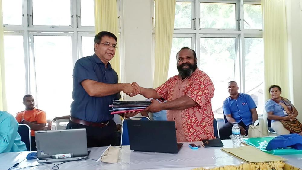 Caption : Koordinator Devisi SDM Papua, Berni Pagawak, saat menyerahkan seluruh hasil laporan Devisi kepada Sekretaris KPA Provinsi Papua, Franky Ivak Dalam.