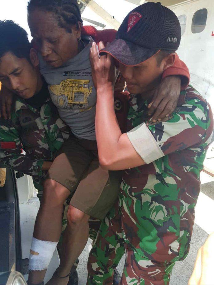 Caption : Dua anggota TNI saat melakukan pertolongan salah satu warga terkena tembak atas kontak tembak di di Kampung Olenki, Ilaga, Kabupaten Puncak-Papua, pada Senin (17/9/2019).