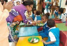 Caption : Bunda PAUD Kota Jayapura, Kristhina R.I.L Mano, S.IP, M.AP saat menyuapi ikan goreng ke salah satu murid PAUD Kencana Waripoi. Foto : Ayu Vhino/PpapuaSatu.com