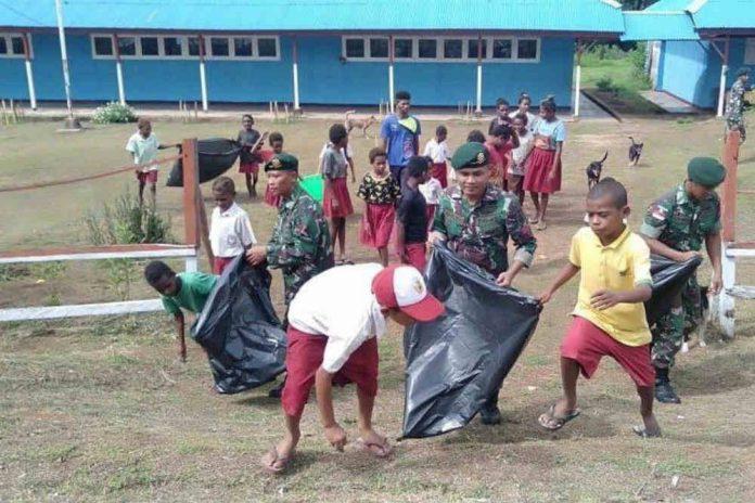 Caption : Terlihat Satgas Pamtas RI-PNG Yonif MR 411/PDW Pos Toray sedang melakukan pembersihan bersama SD YPK Toray di Kampung Toray, Distrik Sota, Merauke, Papua di lingkungan sekolah, Selasa (14/1/2020).