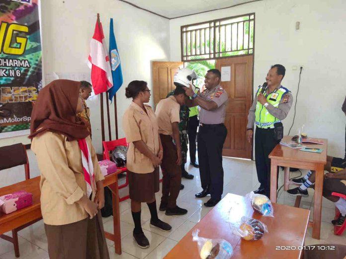 Caption : Kapolsek Abepura, AKP Clief Gerard Duwith, S.IK saat mengenakan helm di kepala salah satu siswa SMA N 1 Abepura kota Jayapura, Senin (20/1/2020) siang