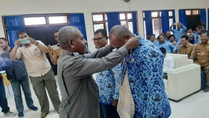 Bupati Jayapura, Mathius Awoitauw saat mengalungkan tanda peserta Musrenbangda Kabupaten Jayapura di Aula Lantai II Kantor Bupati Jayapura, Gunung Merah Sentani, Selasa (17/03/20)