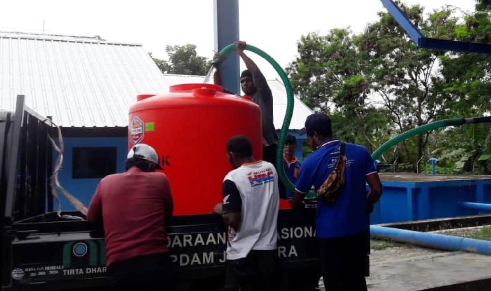 Petugas PDAM Jayapura saat mengisi air ke tangki untuk pengisian di washtafel yang telah dipasang