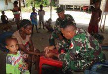 Caption : Personel Satgas TMMD Ke-107 Kodim 1707/Merauke bersama Serka Enjels V. Steven, saat memberikan pelayanan kesehatan kepada masyarakat Kampung Epem, pada Rabu (01/04)
