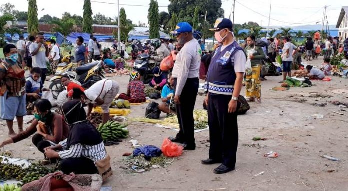 Petugas Dinas Perhubungan Kabupaten Jayapura saat melakukan pemeriksaan penggunaan alat pelindung diri di Pasar Pharaa Sentani