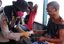 Personil Satgas IV Rehabilitasi Aman Nusa II SDM Polda Papua saat menyerahkan masker kepada warga saat menggelar Bhakti Sosial Polri Peduli Dampak Covid-19 di Kampung Pulau Kosong dan Kayu Pulau, Rabu (27/5/2020)
