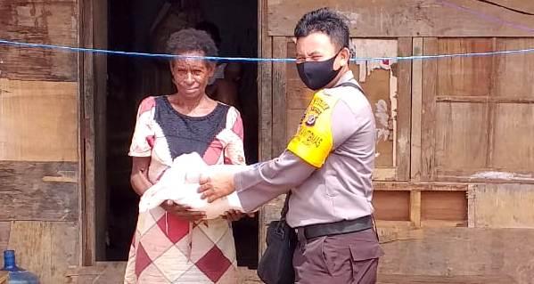 Kapolsek Jair Ipda Fechy J. Ataupah. S.Tr.K saat mendistribusikan beras Polri di Kampung Asikie, Distrik Jair, Kabupaten Boven Digoel, Mingu (31/5/20)