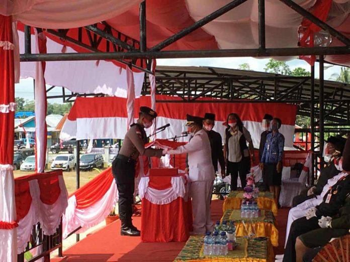 Caption : Bupati Keerom Muhammad Markum, SH., MH., MM saat menyerahkan Bendera Merah Putih kepada petugas pengibar Bendera pada Hut RI ke- 75 Tahun 2020 di lapangan Swakarsa, Senin (17/08/2020).