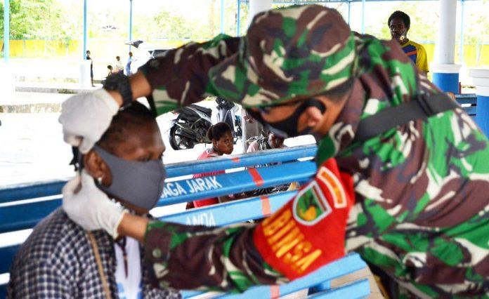 Babinsa Koramil 1710-03/Kuala Kencana, Serda Muhanto saat membagikan masker gratis kepada masyarakat di Pasar Utikini SP13, Distrik Kuala Kencana, Kabupaten Mimika, Sabtu (12/09/2020)